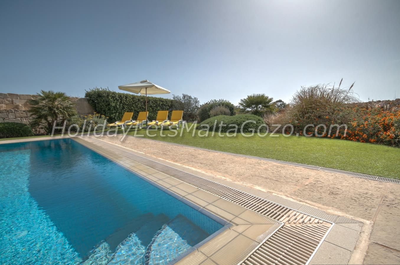 Pool deck/garden with sun loungers